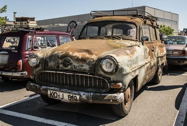 Een oude auto op de parkeerplaats van de commissie