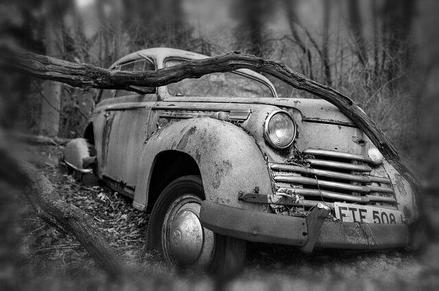 Een oude auto in het bos